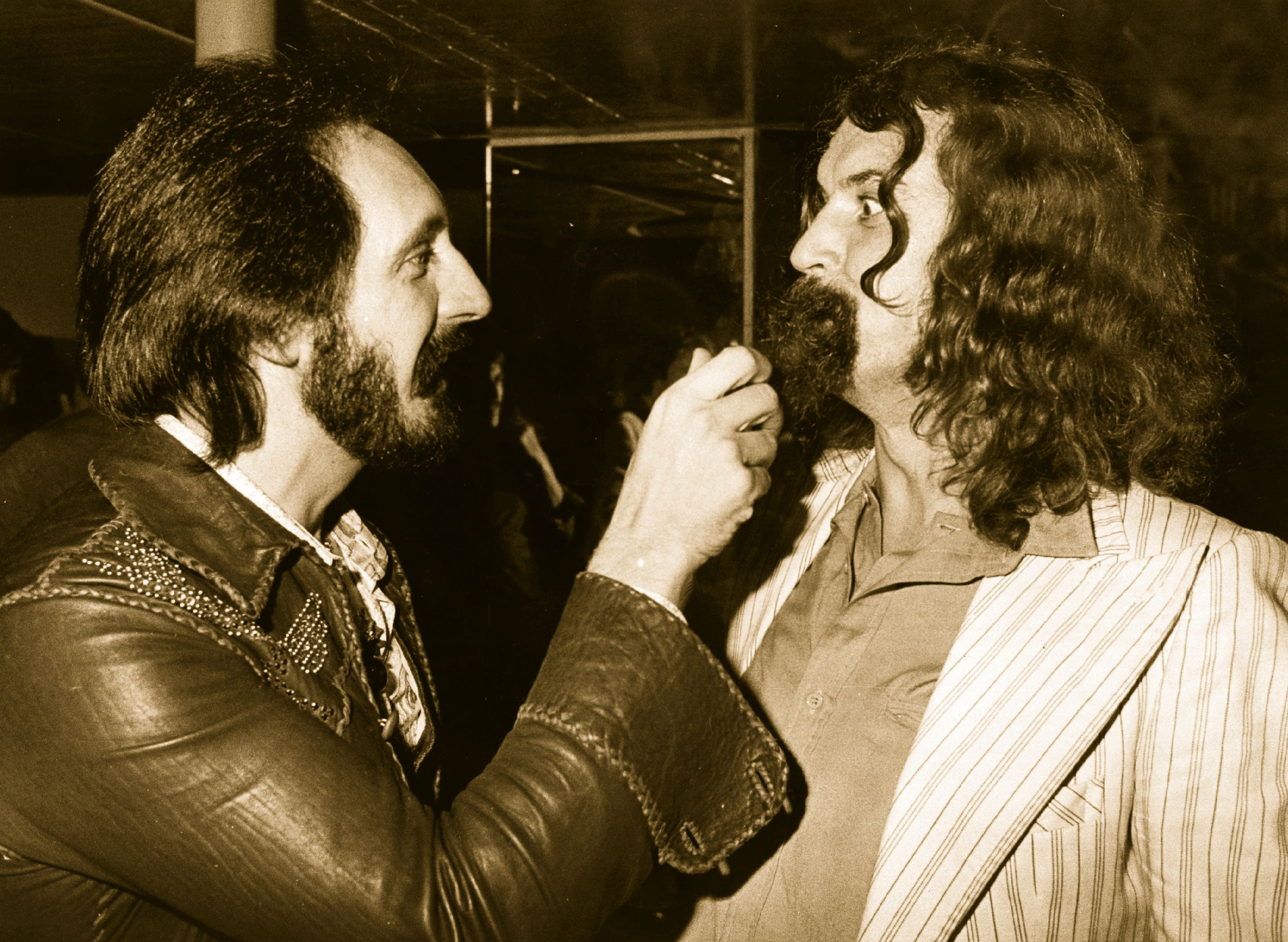 17th October 1979:  John Entwistle (1944 - 2002, left), bass player with British rock band The Who, gives a friendly tug on the beard of Scottish comedian Billy Connolly at the latter's party at the London nightclub Legends.  (Photo by Jon Player/Evening Standard/Getty Images)