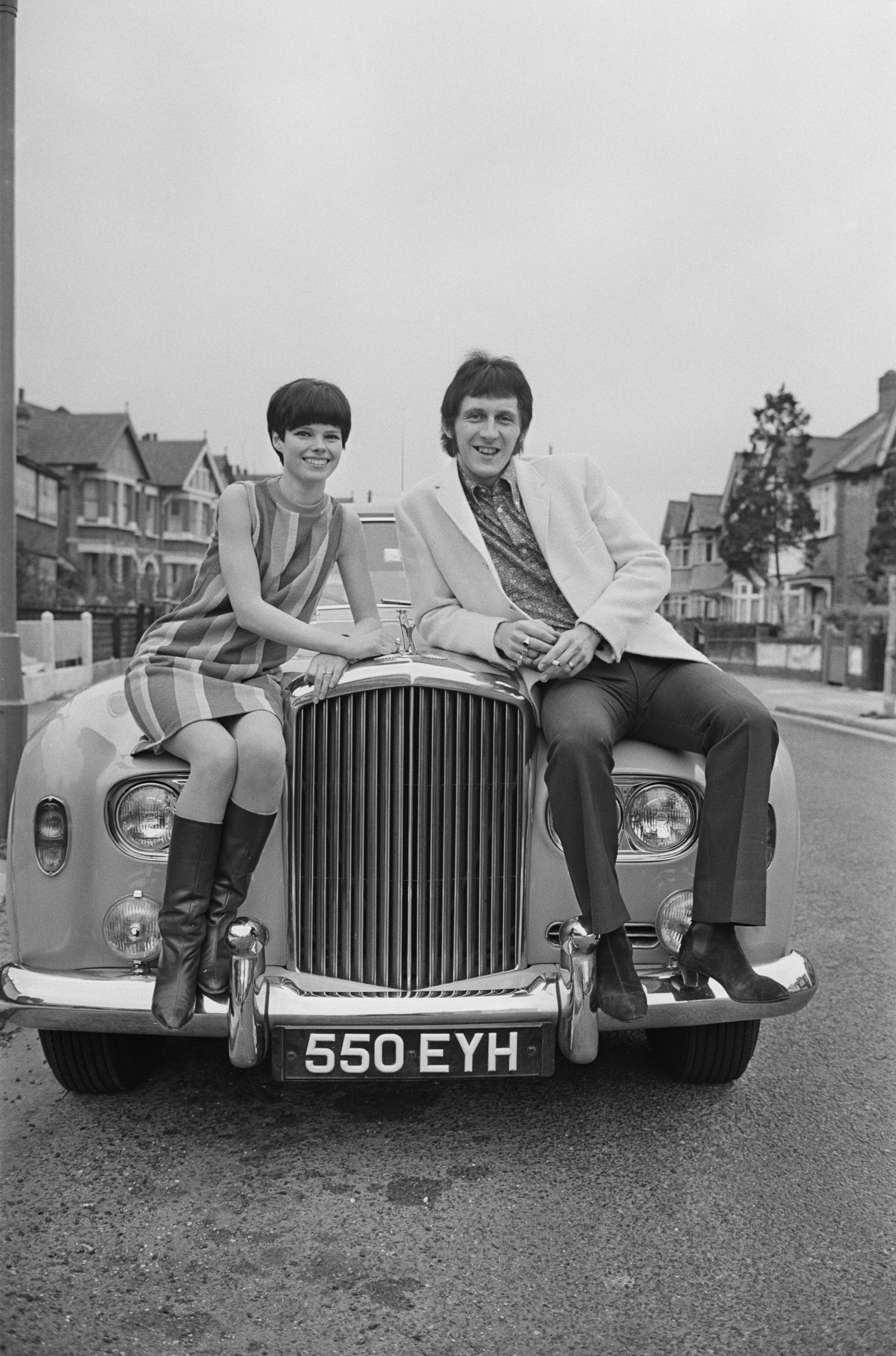 English bass guitarist for 'The Who' John Entwistle and Alison Wise on the bonnet of a Rolls Royce car, 17th March 1967. (Photo by Stan Meagher/Daily Express/Hulton Archive/Getty Images)