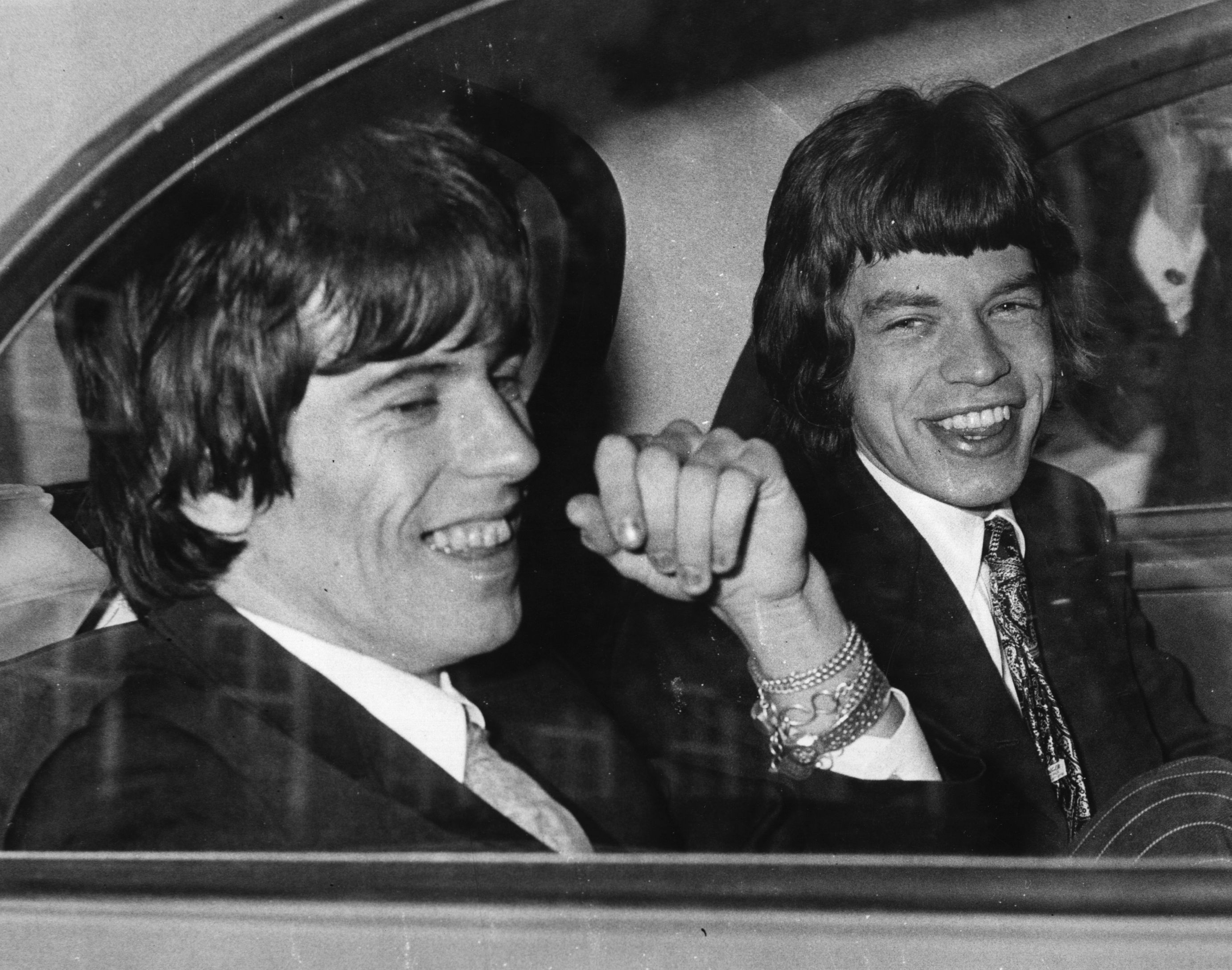 10th May 1967:  Rolling Stones songwriters, guitarist Keith Richards, left, and singer Mick Jagger share a joke in the back of a car as they leave Chichester Magistrates Court where they appeared on drug summonses.  (Photo by Ted West/Central Press/Getty Images)