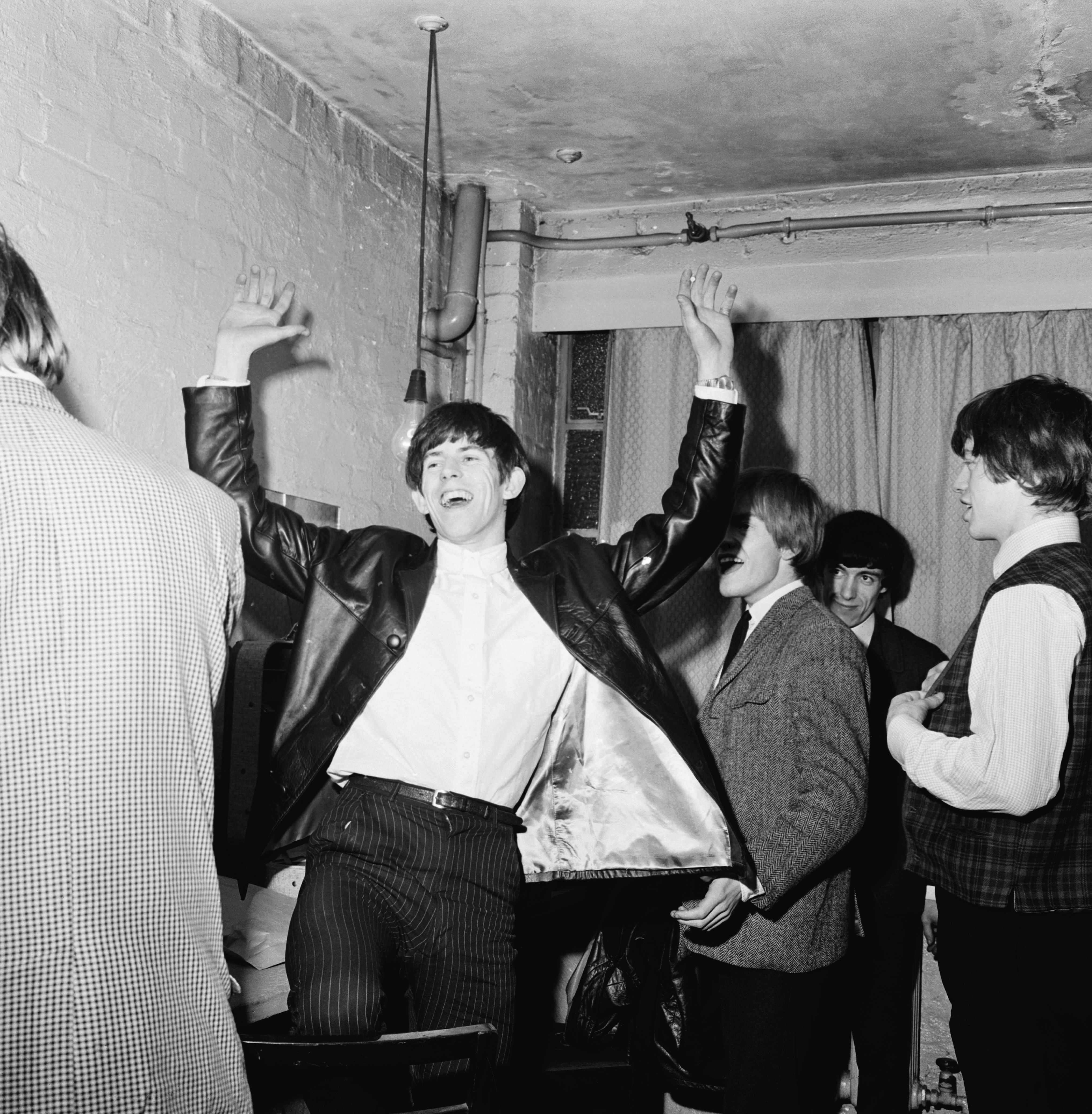 Guitarist Keith Richards laughing with Mick Jagger, Brian Jones and Bill Wyman backstage during an early Rolling Stones tour, December 1963. (Photo by Chris Ware/Keystone Features/Getty Images)